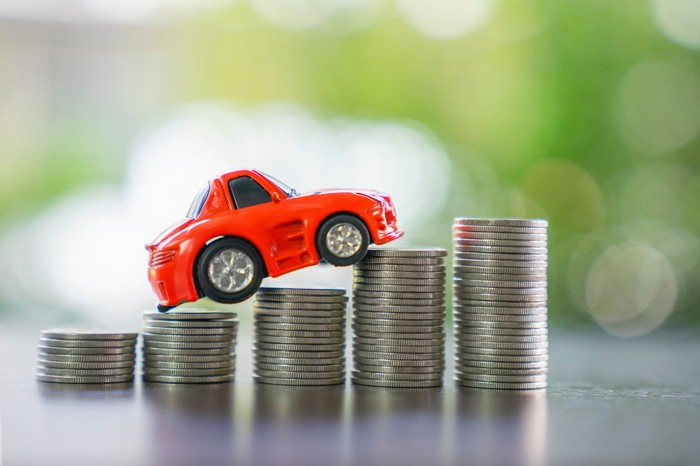 Toy car sits on stacks of coins.