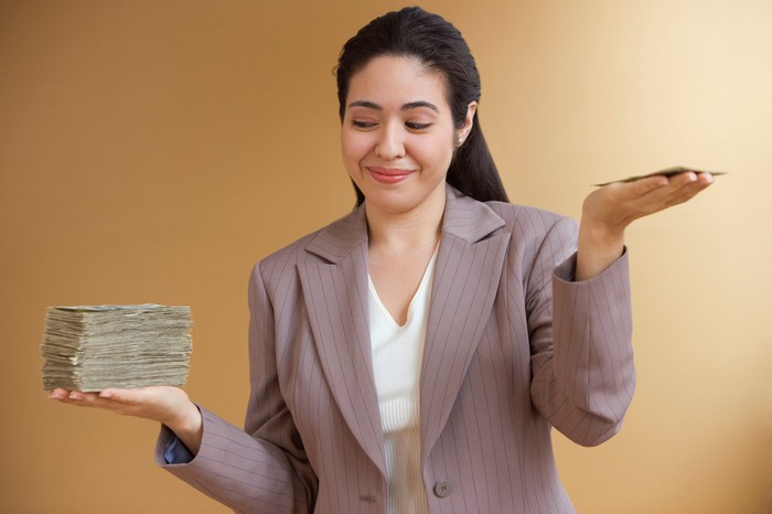 Woman weighing tall cash stack in one hand and short cash stack in the other