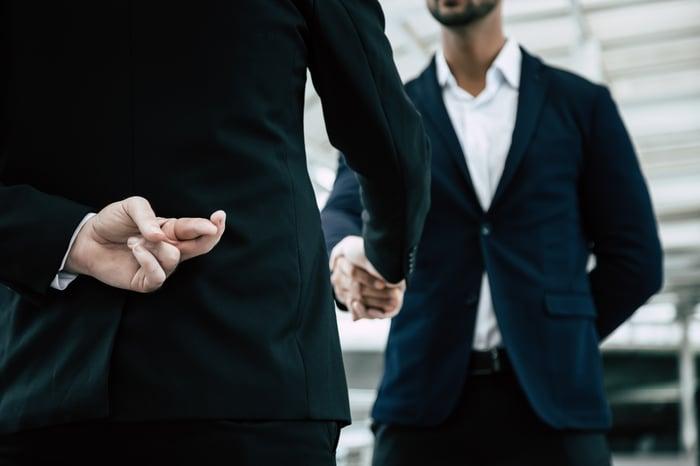 Dois empresários apertam as mãos.  Um deles tem dois dedos cruzados atrás das costas.