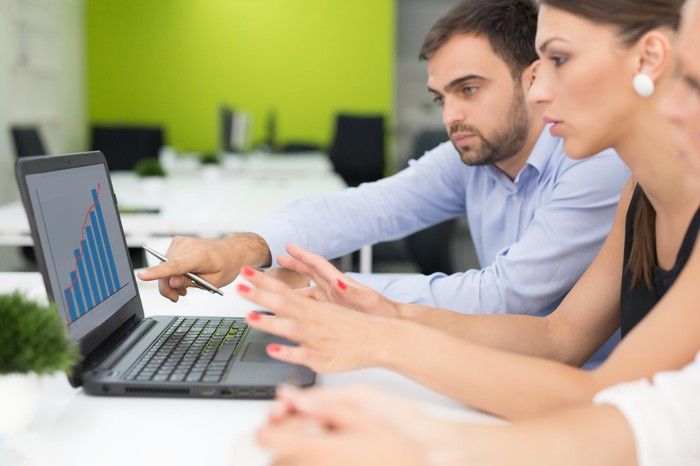 People looking at a chart on a laptop.