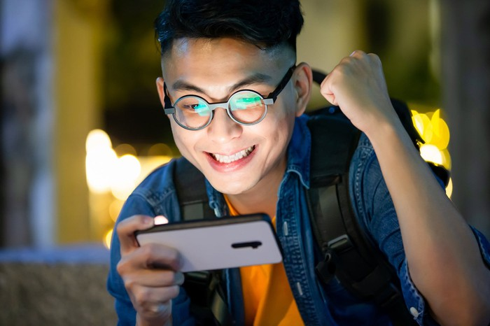 A kid playing a game on his smartphone and smiling.
