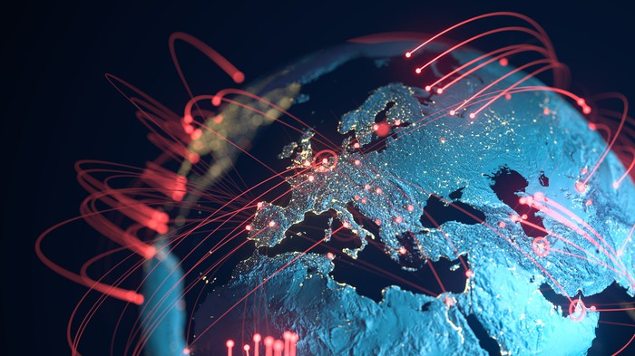 Lasers traveling around the globe indicating transactions and communication.