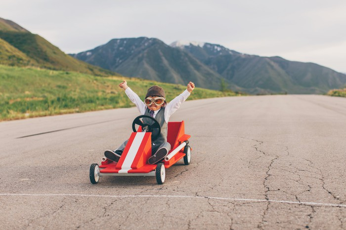 Jeune garçon en costume remporte une course de go cart