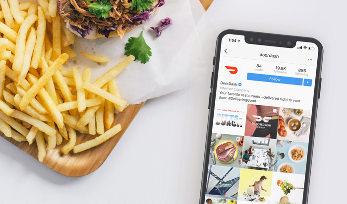 The DoorDash mobile app open on a phone next to a board of fries.