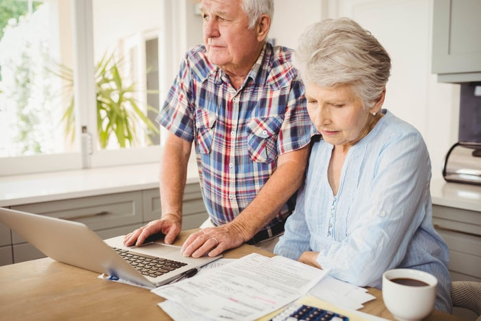 Older man and woman with concerned expressions at laptop with papers next to it