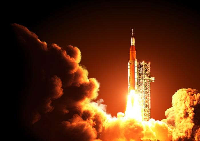 Rocket lifting off a launch pad.