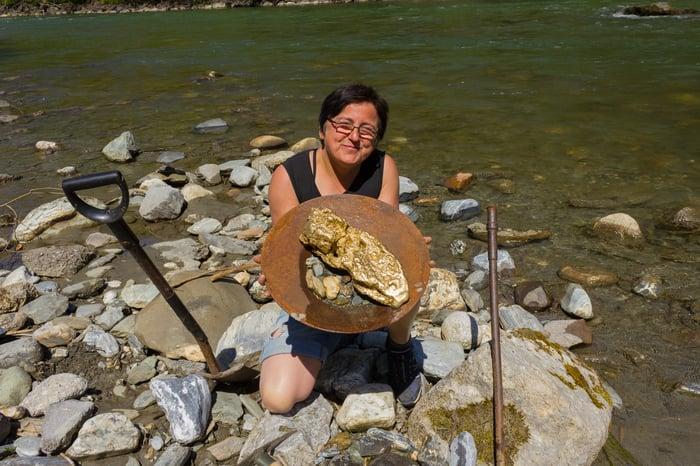 Une femme tient une grande casserole contenant l'or qu'elle a trouvé.