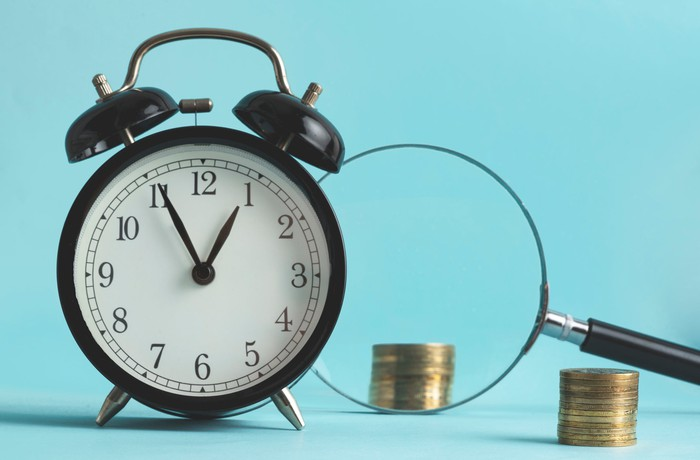An alarm clock beside a magnifying glass and stacks of coins.