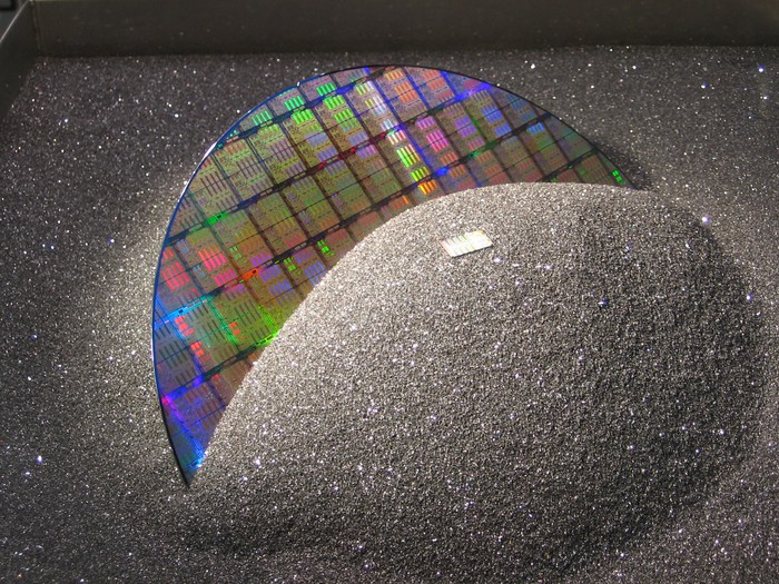 A silicon wafer emerges from a pile of black sand.