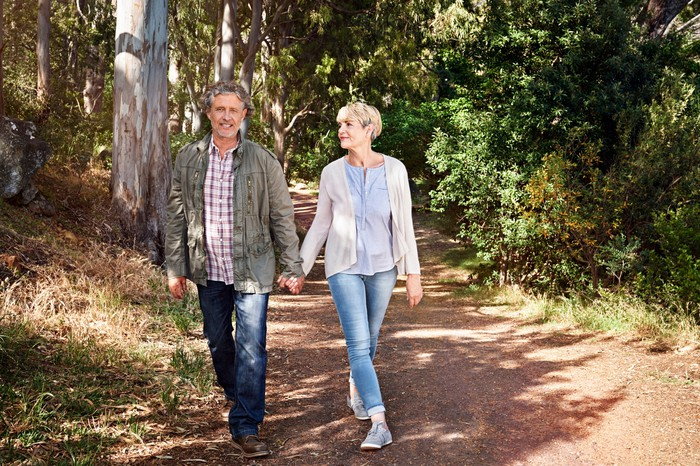Middle-aged man and woman holding hands while walking on trail