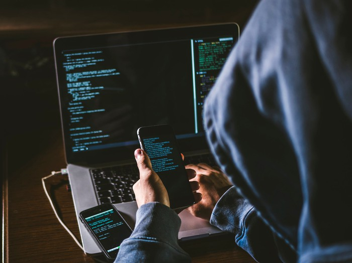 A depiction of a hooded hacker using phones and a PC.