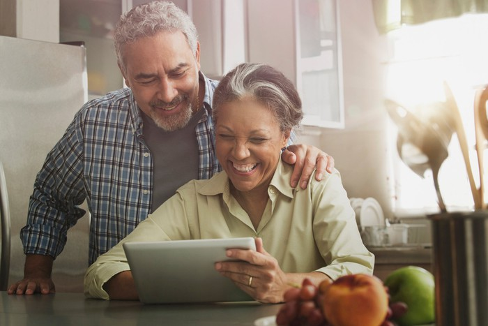 Two smiling people looking at a tablet screen.