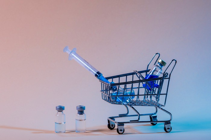 Tiny shopping cart with three vaccine vials and a syringe in it and two vaccine vials next to the cart