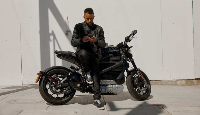 Man leaning against LiveWire One motorcycle