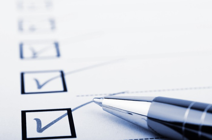 Multiple boxes checked on a checklist, with a pen lying atop the list.