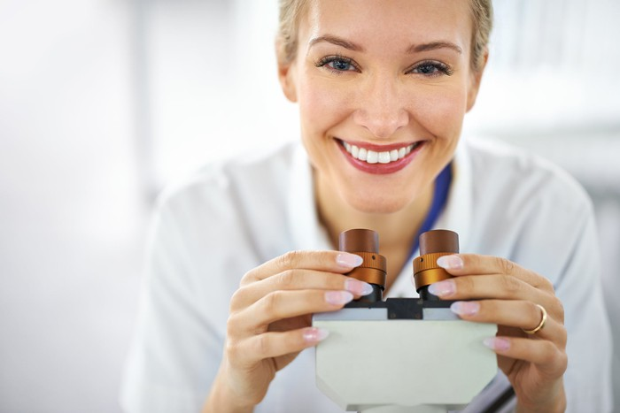 Smiling scientist holding the eyepieces of a microscope