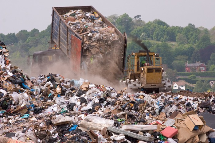 A truck unloads a trailer of garbage at a dump site.