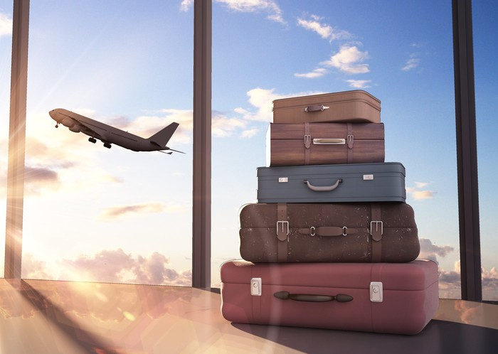 Suitcases are stacked as a plane takes off in the background.