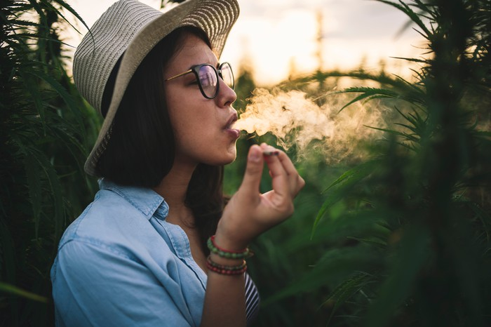 Woman smoking a joint in a plantation.