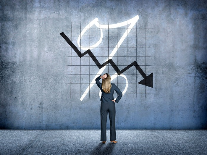 A woman scratching her head as a stock chart moves lower.