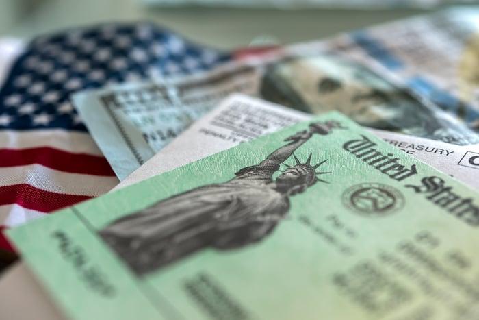 Un chèque de relance placé sur un billet de 100 $ et un drapeau américain.