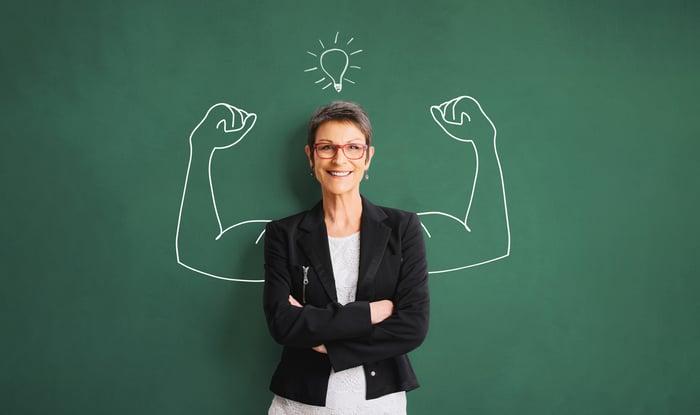 Une femme devant un tableau noir avec un dessin de flexion des bras musclés.