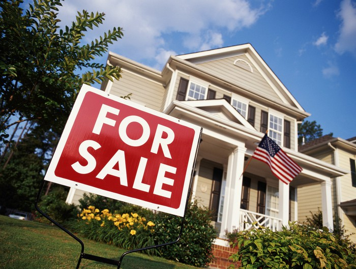 """""""For Sale"""" sign in the front yard of a beige house."""