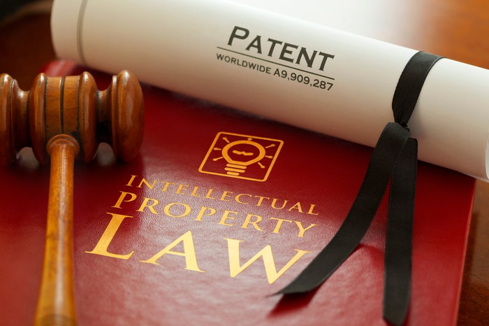 Gavel on book of intellectual property law with patent scroll