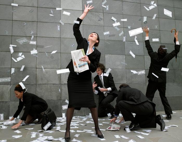 Les billets d'un dollar tombent du ciel sur un groupe d'hommes et de femmes d'affaires.