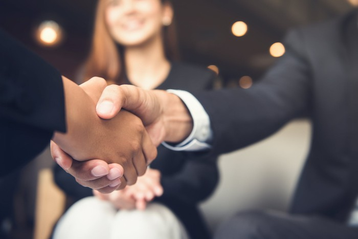Two people in suits shaking hands.