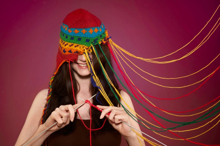 Woman knitting a cap while wearing it