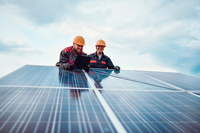 Two men working on solar panels.