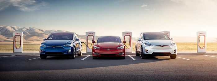 Tesla vehicles lined up next to superchargers