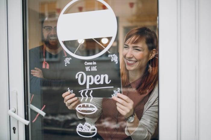 Homme et femme avec panneau indiquant que leur magasin est ouvert.