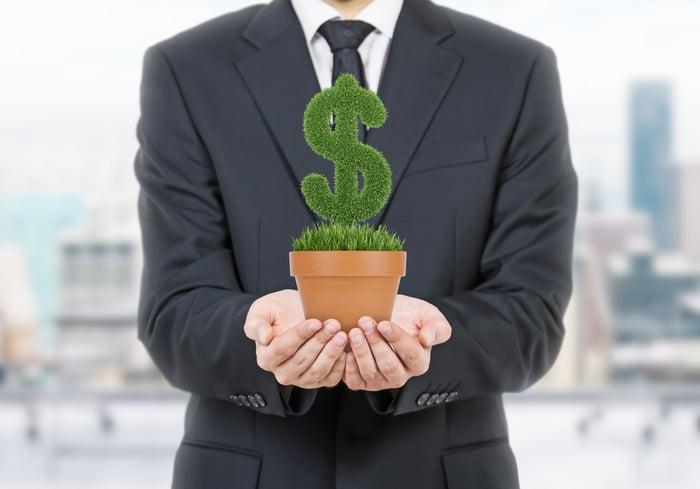 Um empresário segurando um vaso de planta em forma de um cifrão.