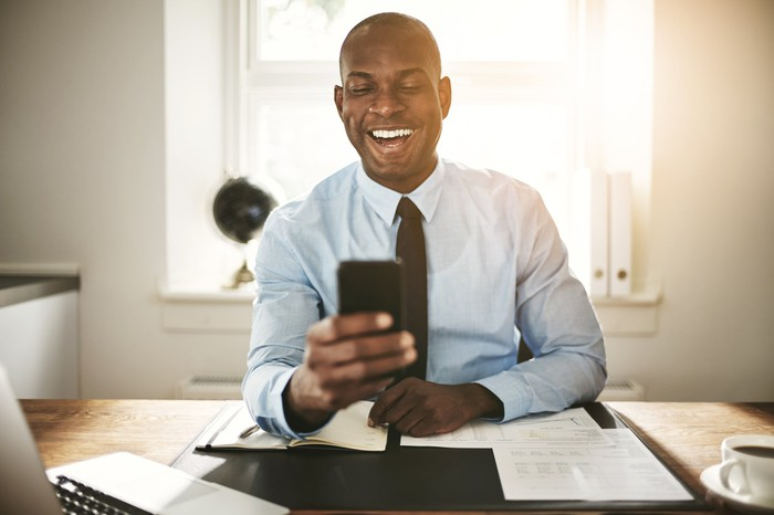 An investor sitting in his office smiles as he looks at his investments on his cell phone.