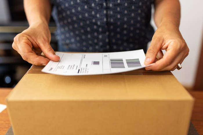 A person's hands placing a shipping label on a box.