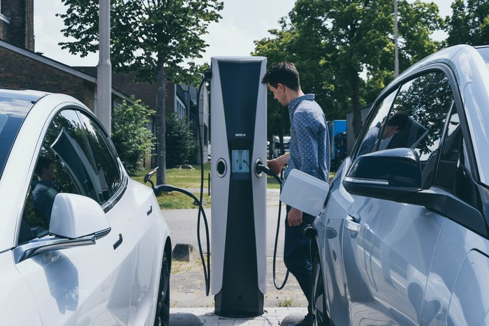 EVBox charging station with man getting ready to plug into his EV