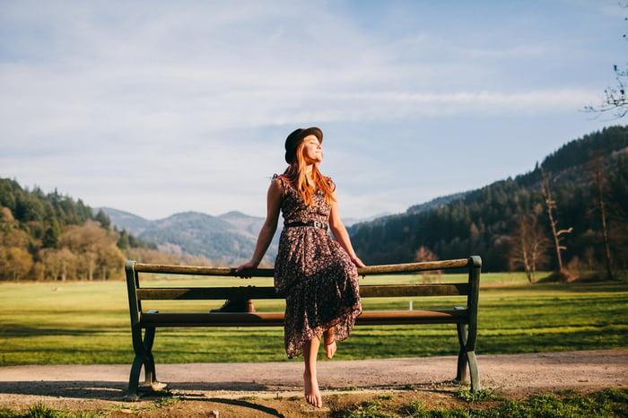 Jeune femme sur un banc de parc un jour de printemps.
