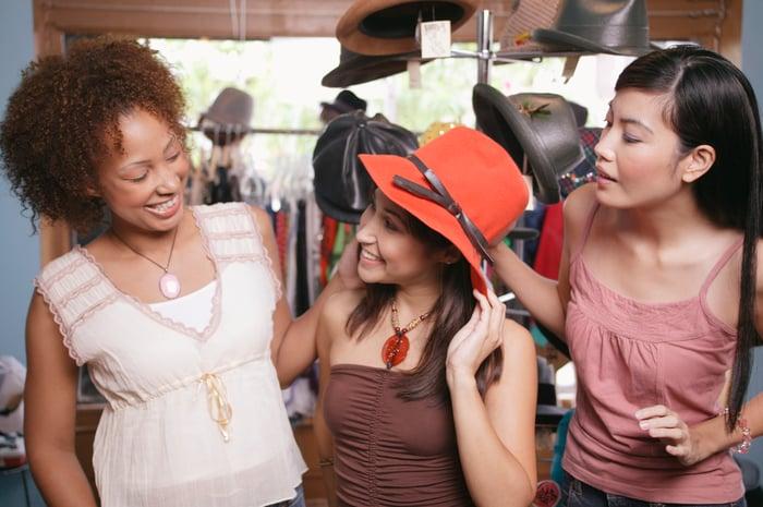Trois acheteurs souriants dans un magasin de chapeaux, l'un d'entre eux essayant un chapeau.