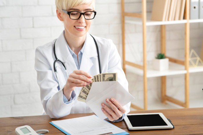 Smiling doctor sitting at a table, holding an envelope filled with cash.