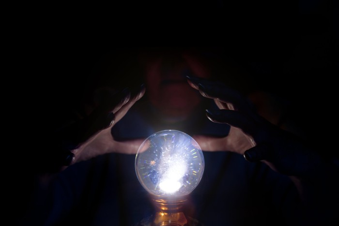A wizard using a crystal ball in the dark.