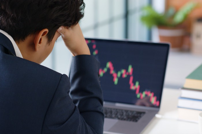 A man in a suit sitting at a desk looking at a chart that shows a stock going down.