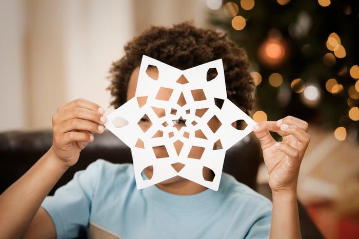 Little boy peering through a paper snowflake.