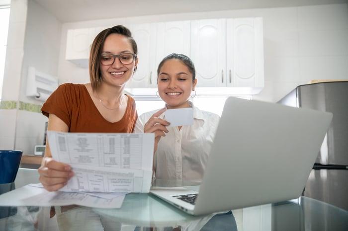 Un couple examine ses finances avec un ordinateur portable et une feuille de calcul.