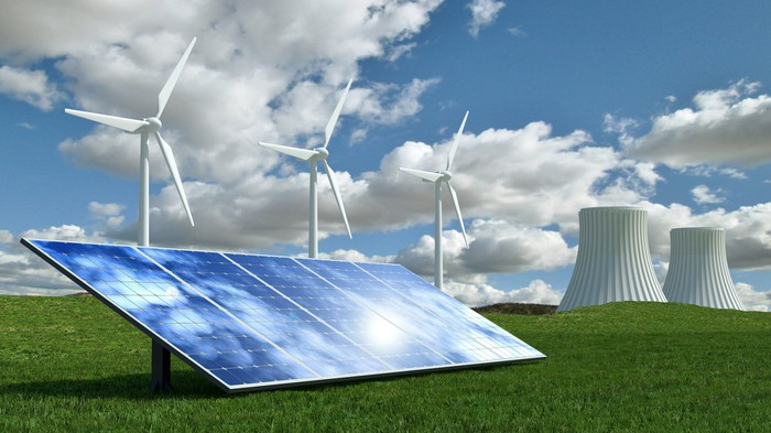 Windmill and solar panels and a nuclear power plant set against a blue sky