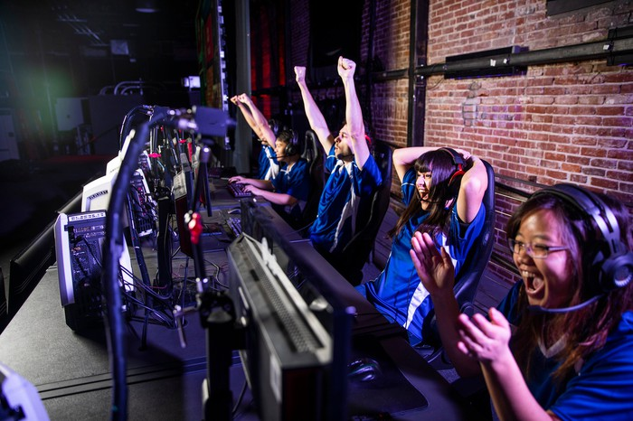 A team of people playing an online game cheer.