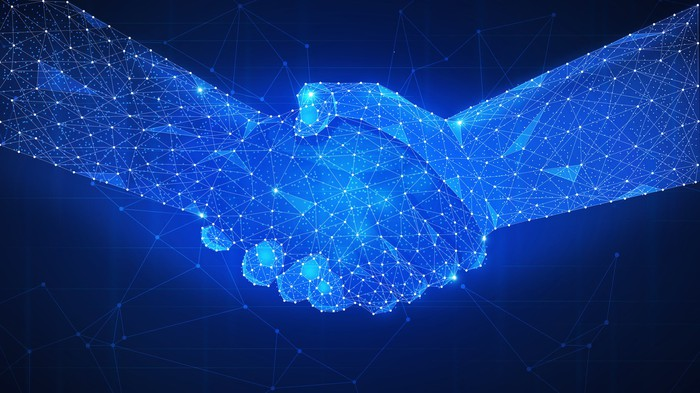 Two hands, made out of digital networks, form a handshake.