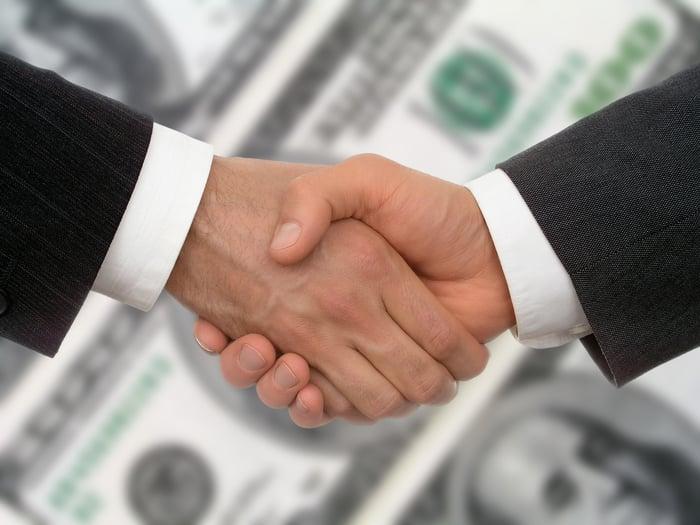 Hands shaking in front of $100 bills