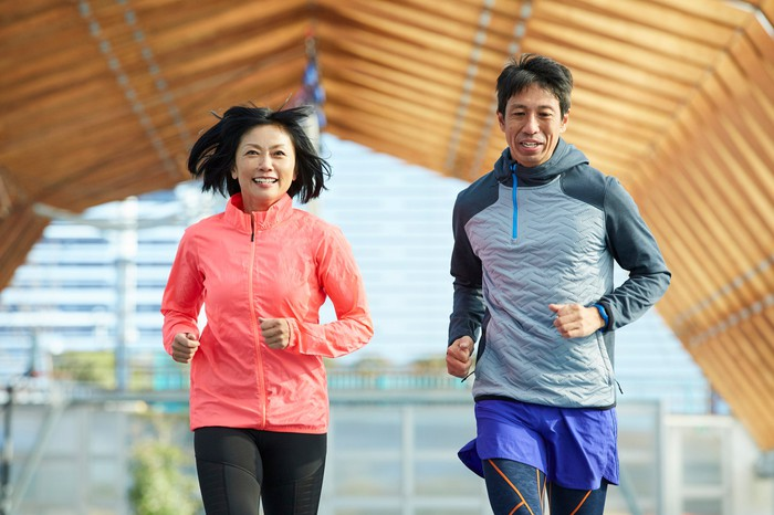 Two people jogging and smiling outside